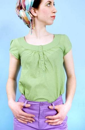 Grön blus från MQ, 299 kr. Lila byxor från Åhléns, 249 kr och en rutig scarf från MQ för 249 kr.