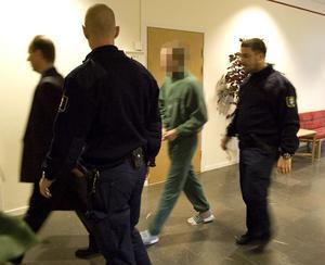 En av de misstänkta gärningsmännen leds in i rättssalen. Bilden är tagen den 29 oktober, då rättegången mot de två männen inleddes.Foto: Arkiv/Lars Sundin