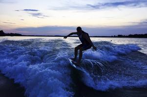 Patrik Sandell surfar i kvällsskymningen.