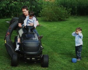 Pappa o storebror klipper gräset medan lillebror tycker det låter väldigt illa..