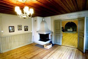 I ett av rummen på nedervåningen finns öppen spis, bröstpanel och vackra väggmålningar.