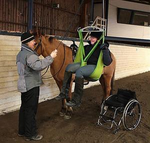 Nu kan Kristina Ulander äntligen ta sig upp på hästryggen igen med hjälp av handikapplyften och assistens från sin ledsagare Berith Uhlin.