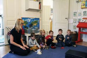 Madeleine Östling sitter en stund med barnen under dagens inledande sång- och musikstund.