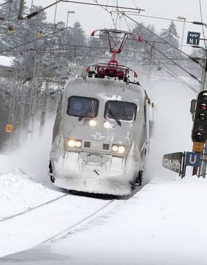 Bättre fart. I ett moln av snö passerar SJ:s Västeråsbyggda X2000-tåg Flemingsbergs station söder om Stockholm. Tisdagen innebar att fler tåg kunde ta sig genom snön - men onsdagen innebär trots det många inställda tåg. FOTO: SCANPIX