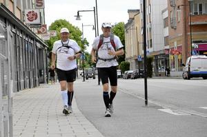 Långöpare. Inget avslöjar att det är två långlöpare som joggar fram på Storgatan i Hallsberg. Efter en natts sömn på Stinsen väntar omkring fyra mils löpning.