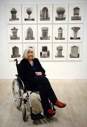 Hilla Becher framför en av makarna Bechers fotoserier på vattentorn.