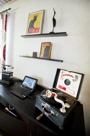 Nytt möter gammalt. Vevgrammofon och en telefon från forna tider flankerar datorn som står på en svartlaserad ekskänk.
