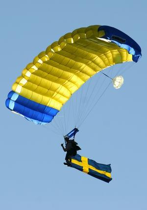 Annorlunda flagghissning. Kvällens höjdpunkt var kanske ändå när fallskärmshopparen dök upp under solen och landade mitt på kaserngården med den svenska flaggan.