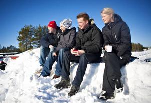 NJÖT. Andreas Flinck, Oscar Johansson, Pontus Widing och Filippa Widing njöt av värmen och utsikten över bilarna från en snöhög.