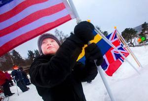 Alexander Sandin sätter den amerikanska flaggan i snön efter OS-invigningen.  Foto: Håkan Luthman