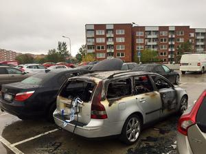 Två bilar började brinna på en parkering i Nacksta under natten mot lördagen.