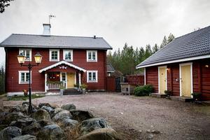 Huset ligger pampigt på en höjd med ett stort gårdshus intill.