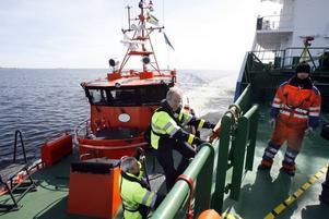 Anders Thyr håller i lejdaren så att lotsen Mats Wallman säker ska kunna ta sig ombord på tankfartyget.