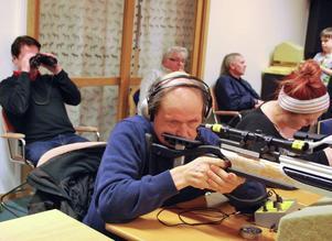 Janne Smångs är syndskadad och siktar med hjälp av ljudsignaler. Ledsagaren Kjell Andersson kikar på resultatet.
