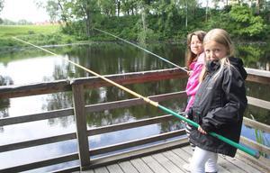 Emilia Olofsson, 9, och Maja Sandelin, 8, tycker inte om att vuxna kommer till Dal Britas damm om kvällarna och tjuvfiskar.
