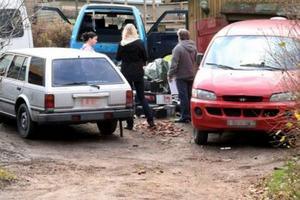 Miljöinspektörer från Degerfors kommun ses här tillsammans med fastighetsägaren där det ligger cirka 50 bilbatterier slängda på tomten.