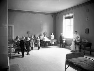 En interiör. Syster Löfgren med sjuka barn. BILD: Troligen SAM LINDSKOG, källa Örebro läns museum.