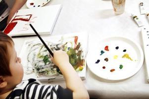 Treåriga Linus Lundsten satt djupt koncentrerad när han lät penseln fara fram över duken.