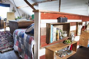 Mellan sovrummet och vardagsrummet finns en hemmabyggd rumsavdelare som fungerar som förvaring och ryggstöd för soffan på andra sidan.