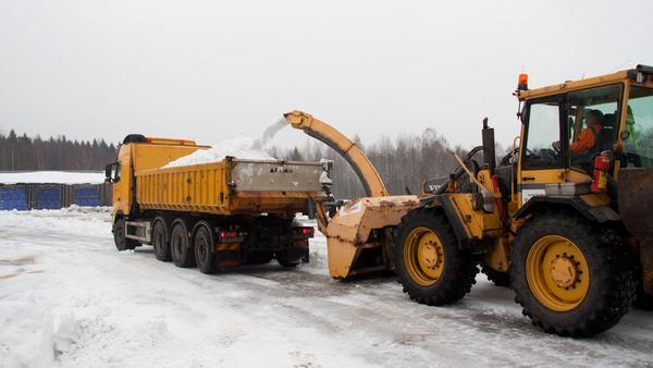 Lastbil efter lastbil lastas med snö för att få i ordning spåren.