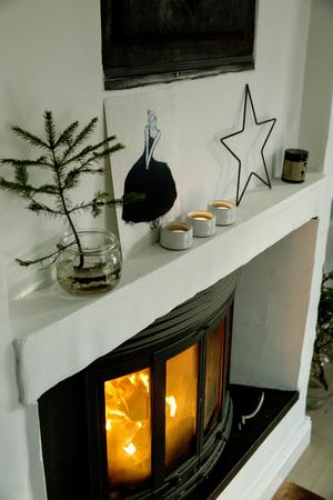 Eld i spisen är en del av julkänslan, och doftade granskott trivs fint i glasburkar med vatten.