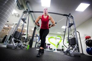"""När Innerjoy öppnar om någon månad så gör de det i hård konkurrens – och ibland med andra nystartade gym. Fristilen är ett relativt nystartat gym men har redan trogna medlemmar. Marie Olsson tränar hårt för att hålla sig i form och för att rehabilitera sig. """"Jag är sjukskriven och behöver träna upp min axel. Det gör att det känns mycket bättre"""", säger hon. Foto: Håkan Luthman"""