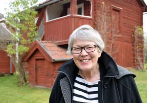 Kersti Jobs Björklöf framför källarstugan på Knisgården, en gård som numera bebos av hennes son och hans familj.