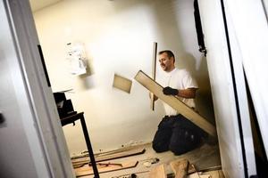 Snickaren Peter Borg bryter upp parkettgolvet i ett av Industriprofils vattenskadade rum.
