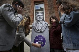 Folk lyssnar till statyer som pratar i London.