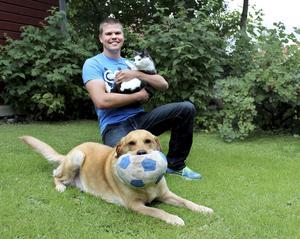Av fem familjemedlemmar är tre på bild. Stefan Tallgren håller i katten Skrutten och blandisen Nellie visar sina anlag som apportvillig fågelhund.