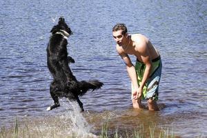 Christian Sörensen och hunden Wilma värmer upp inför simningen i baddammen i Tjärnbärcka.