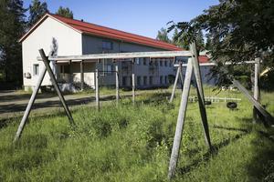 Igenvuxen lekpark med trasiga gungor på skolgård vid stängd skola i Kalix kommun i Norrbotten.