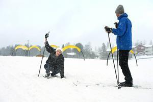 Baker försöker få ordning på skidor och stavar.