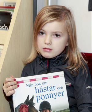 Alicia Åhlén läser en bok om dagen och drömmer om att bli frisör.