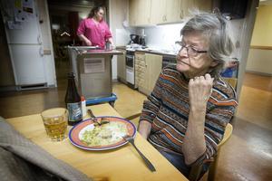 Undersköterskan Cornelia Ivansson serverar trettondagsmiddag till Barbro Nilsson på Blomstergården i Krokom.