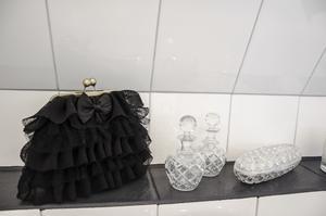 Detaljer vid badkaret. Gammeldags parfymflaskor och en franskinspirerad börs i spetstyll.