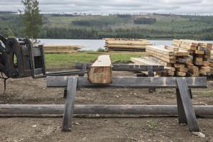Med hjälp av traktor och sågbockar kommer timret på rätt höjd.