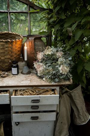 På den dekorativt slitna arbetsbänken i växthuset står en nygjord höstkrans med hortensia.