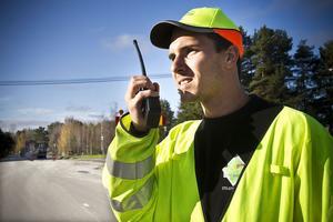 Daniel Hovstedt är trafikvakt och ser till att trafiken flyter på som den ska under tiden asfalten läggs.