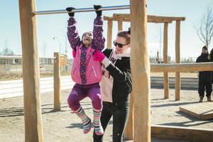 Stenhamreskolans fritidsavdelningar firar påsklov på  Östernäs nya lekplats. Lina Svedin, arbetsledare, hjälper Aryana.