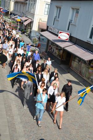 Efter fanbärarna tågar Karlsängskolans elever och personal mot avslutningen i Nora kyrka.