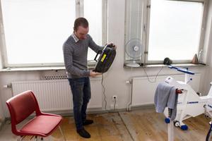 Henrik Öijer, ordförande i Falu CK, skakar vattnet ur en radio, som olyckligt nog stod på golvet när skyfallet kom.