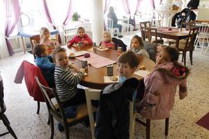 Dagisgruppen Grodan njuter av saft och bulle på Kafé Chocolate i Rimbo. På väggarna hänger deras vårkonstverk.