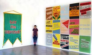 "Lisa Jonasson på Konstcentrum mellan textilen ""Say the obvious!"" och en serie affischer i screentryck"