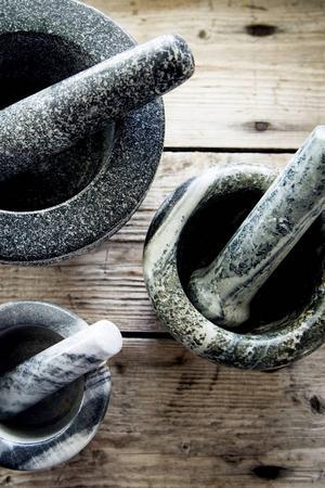 Mortlar i olika storlekar på ett välanvänt träbord.