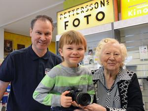 Petterssons Foto har dammat av den gamla skylten från 1950-talet och blivit Petterssons Foto i gen. Fr v ägaren Gunnar Mattsson, sonen Markus samt moster Gun Pettersson, 91, som var med redan då firman etablerades i Malung 1925.