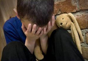En liten pojke gråter med sitt gosedjur. (Bilden är arrangerad).