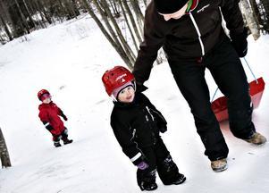 Majken Lönn har dubbla lekhjälmar – en med vitt spänne hemma och en med grönt på förskolan. I bakgrunden syns storasyster Astrid och till höger pappa Magnus.