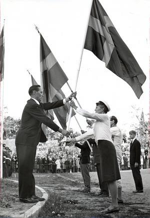Svenska flaggans dag firas på Djäkneberget 1965. Gymnastikdirektör Josua Westin överlämnar fana till fru Gerda Eriksson, Västerås damkör.