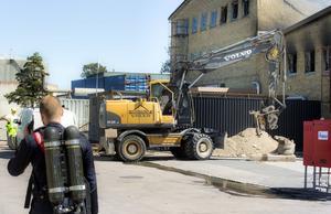 Grävmaskiner på plats arbetar med att gräva efter elkablar och vattenrör.